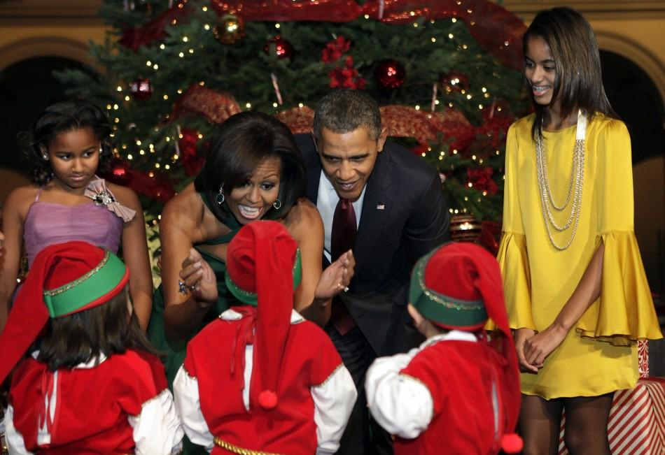 "U.S. President Barack Obama, first lady Michelle Obama and their daughters Sasha (L) and Malia greet children, dressed as elves, at the ""Christmas in Washington"" celebration at the National Building Museum in Washington"