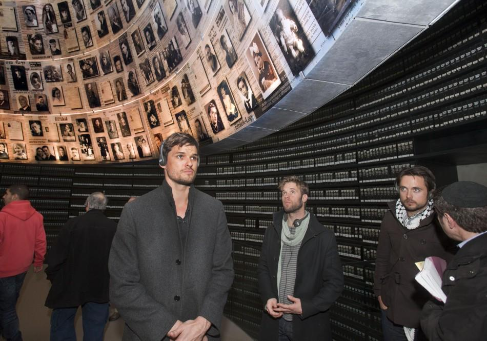 Hollywood actors Austin Nichols (L), Shaun Sipos (C) and Justin Chatwin (R) look at pictures of Jews killed in the Holocaust during a visit to the Hall of Names at Yad Vashem's Holocaust History Museum in Jerusalem