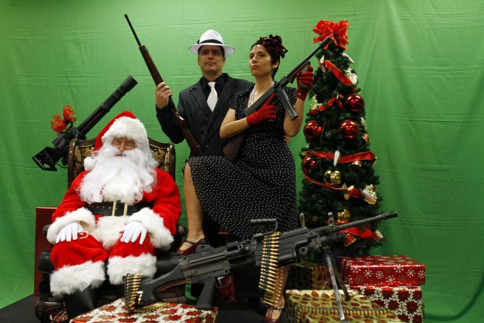 Todd Engle (C) and Mary Rose Engle (R) hold weapons as they pose for a photograph with a man dressed as Santa Claus at the Scottsdale Gun Club in Scottsdale, Arizona December 10, 2011.