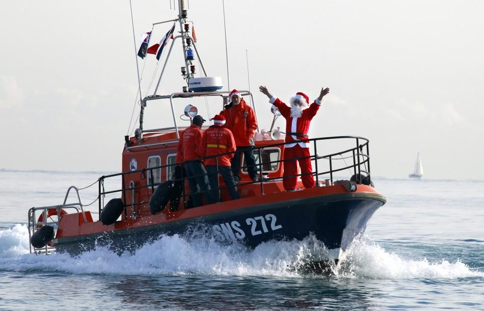 A man dressed as Santa Claus waves aboard a sea rescuers boat during the traditional Christmas bath in Villeneuve Loubet, southeastern France