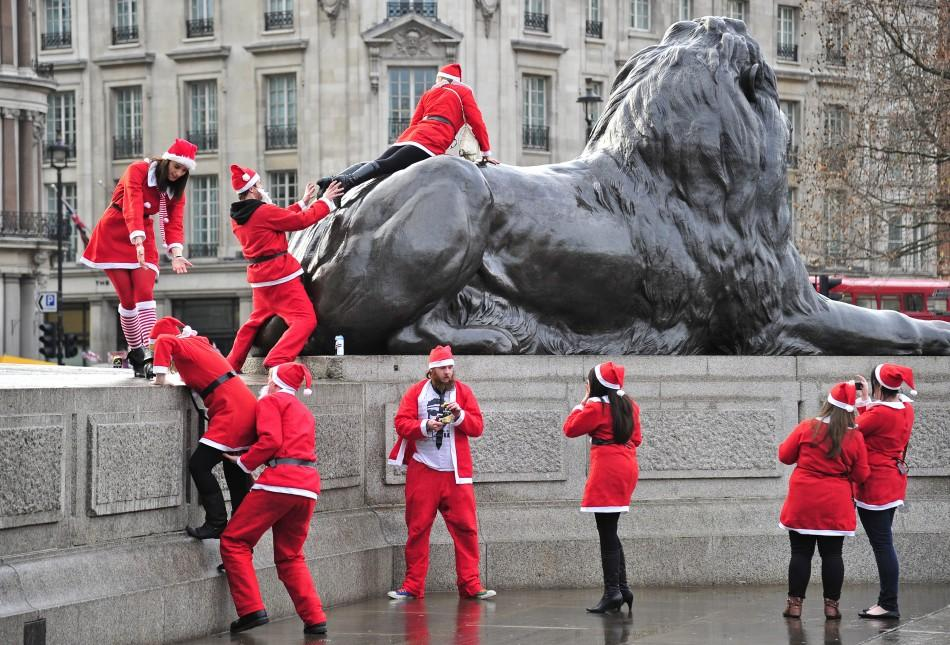 Revellers taking part in a 'Santa pub crawl' dressed in seasonal costumes climb on statues in Trafalgar Square in London.
