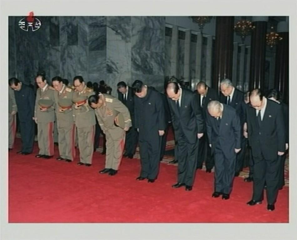 New North Korean ruler Kim Jong-un (4th R), high level party members and generals bow as they pay their respects to former leader Kim Jong-il lying in state at the Kumsusan Memorial Palace in Pyongyang in this still picture taken from video footage of sti