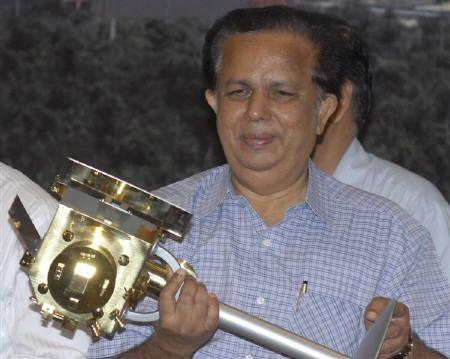 Former Chief of ISRO G. Madhavan Nair, holds a miniature of India's first unmanned moon mission 'Chandrayaan-1' after its launch