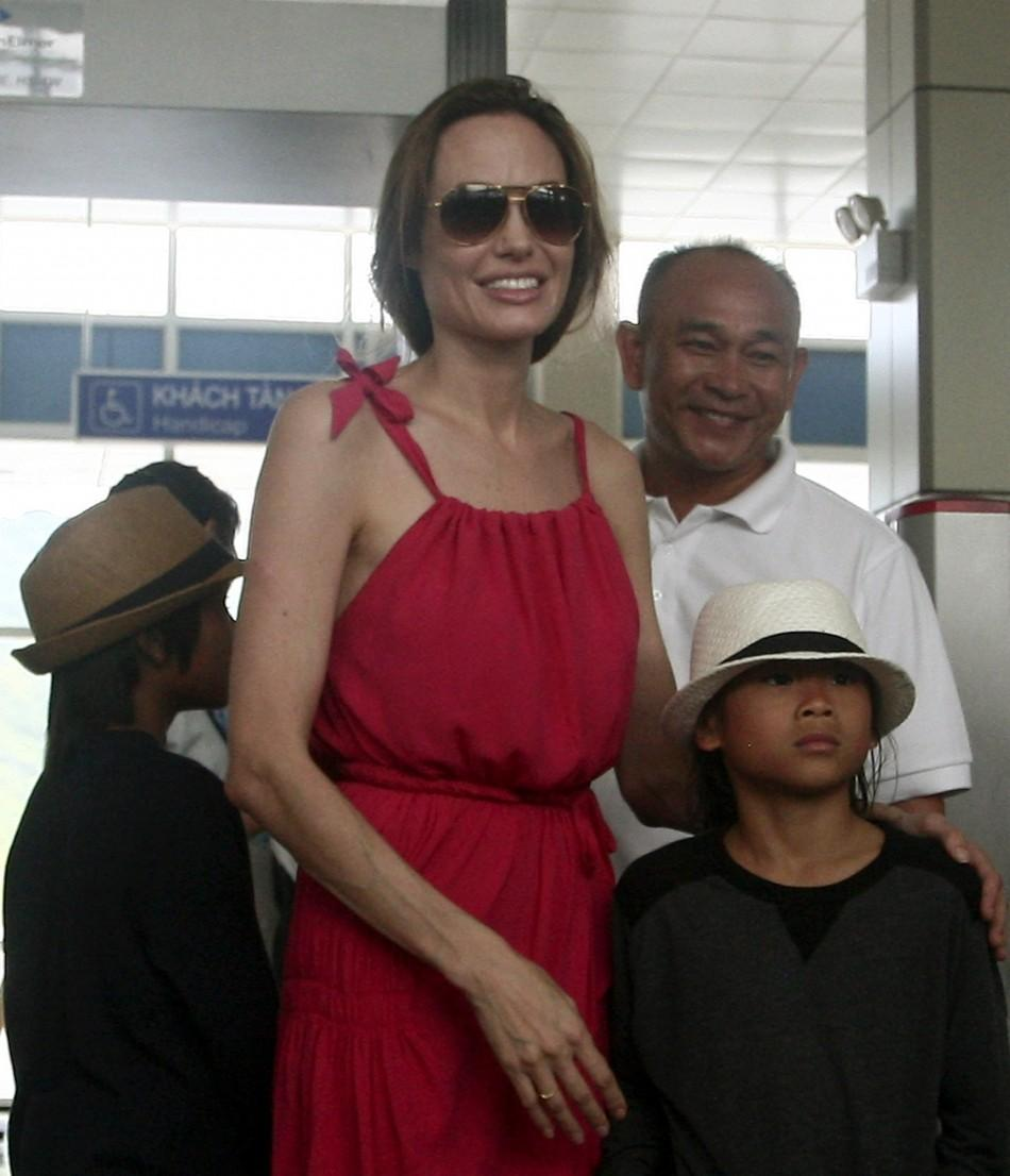 Angelina Jolie stands with her adopted son Pax Thien from Vietnam at a security check point before leaving Con Dao island