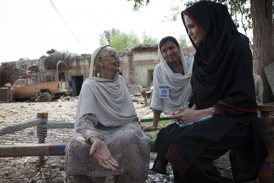 Angelina Jolie meets 64-year-old Zenul Hawa at her flood damaged home in the village of Mohib Bandi