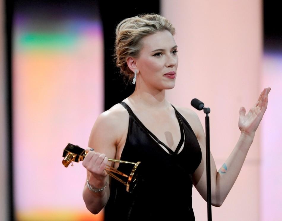 """US actress Scarlett Johansson holds her trophy for Category """"Best International Actress"""" during the 47th Golden Camera award ceremony in Berlin February 4, 2012. The Golden Cameras (Goldene Kamera) are awarded by a popular German TV-magazine hon"""