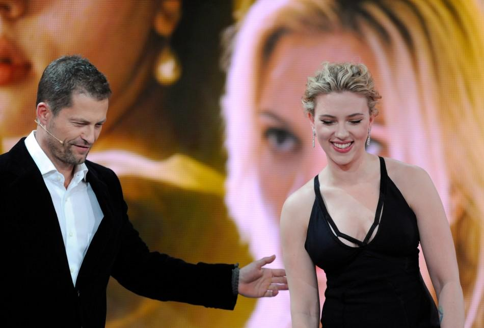 """US actress Scarlett Johansson leaves the stage after being awarded by German actor Til Schweiger for category """"Best International Actress"""" during the 47th Golden Camera award ceremony in Berlin February 4, 2012. The Golden Cameras (Goldene Kamer"""