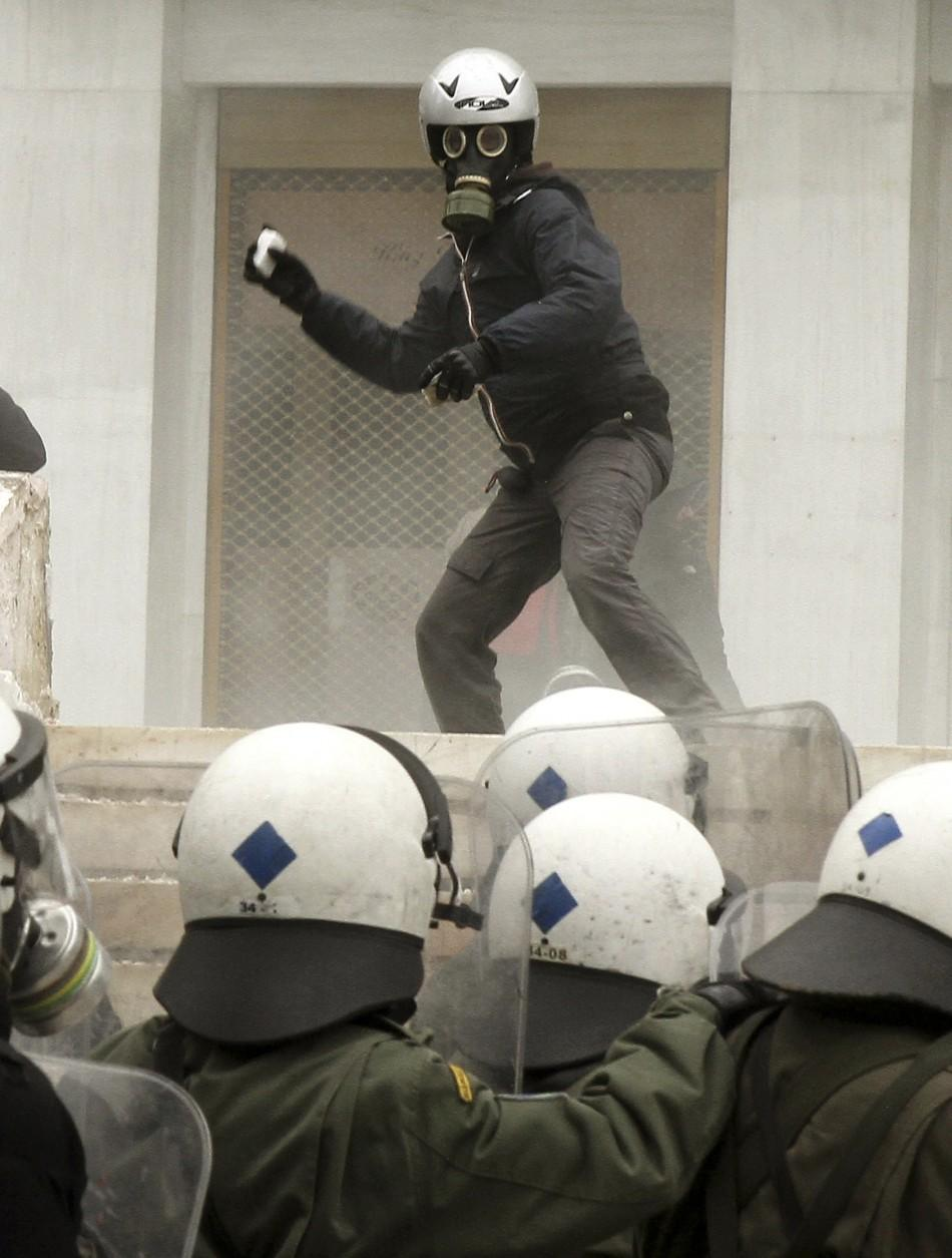 A protester hurls rocks at riot police in Athens Friday