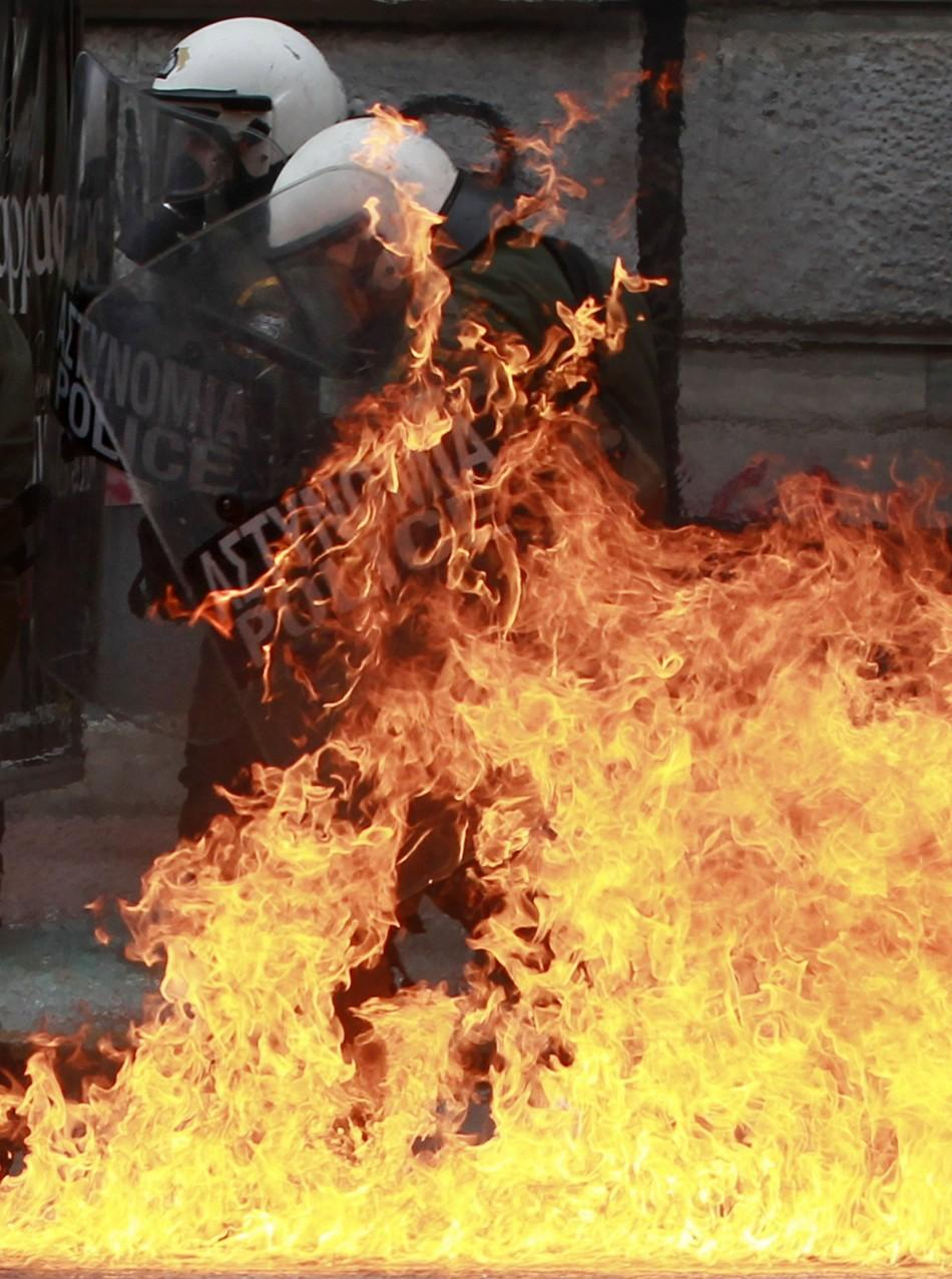 A riot police officer is set aflame by a gasoline bomb hurled at him during Friday's Athens protests