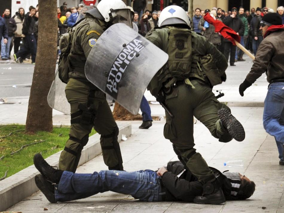 A riot police officer kicks a downed protester during demonstrations in Athens Friday