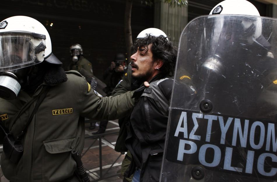 Police detain a protester during demonstrations in Athens Friday