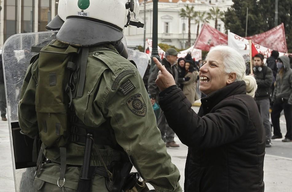 A woman confronts a riot police office during demonstrations in Athens Friday