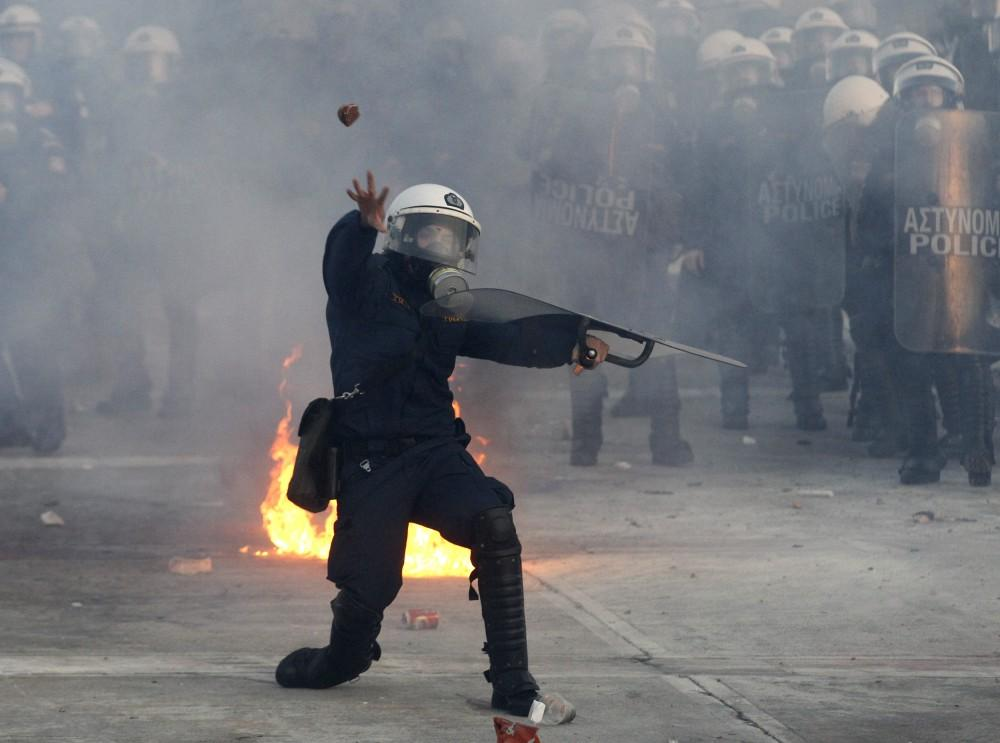 Greece: Blurring the line between demonstrators and peace officers, a Greek policeman throws a rock at protesters Sunday.