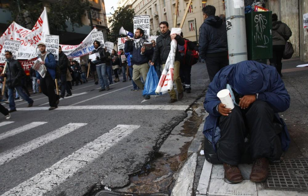 Greece: A homeless man begs for money as a demonstration against economic austerity measures passes him by in Athens Sunday.