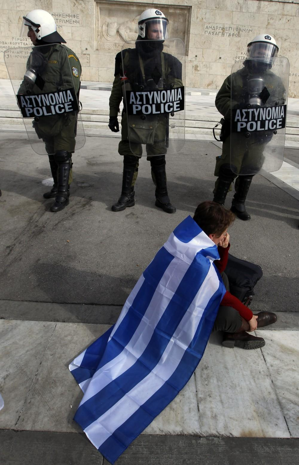 Greece: A demonstrator sits in front of officers guarding the country's parliament in Athens Saturday.