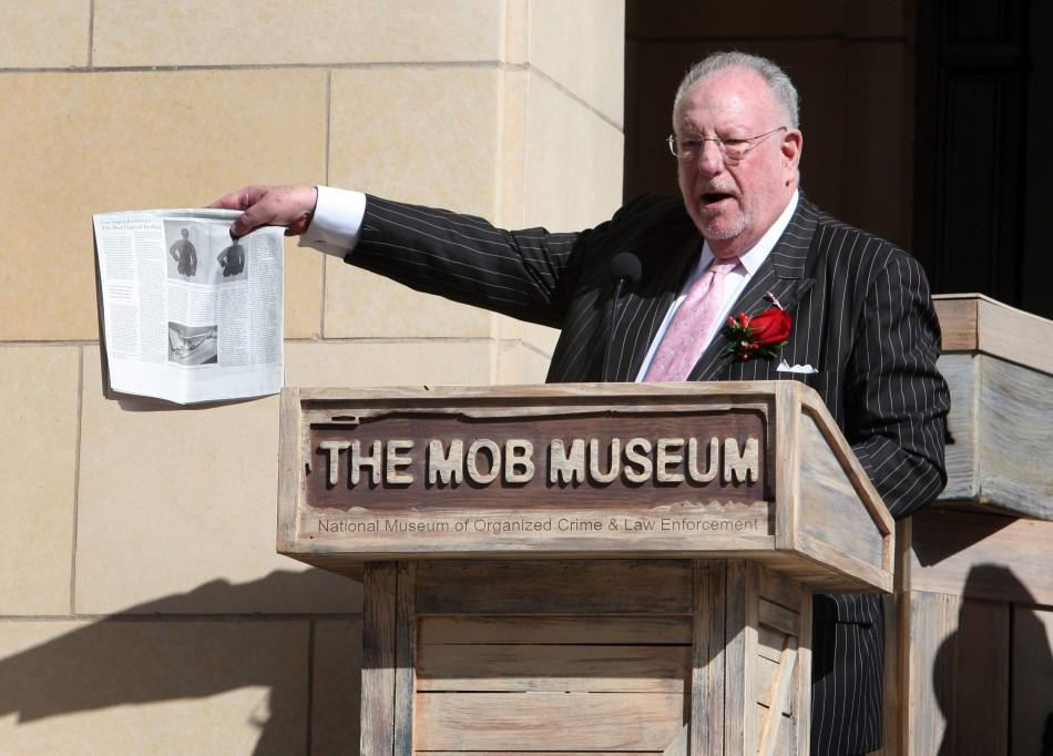 Former Las Vegas Mayor Oscar Goodman holds up a news article with a story on The Mob Museum during the museum's grand opening in Las Vegas