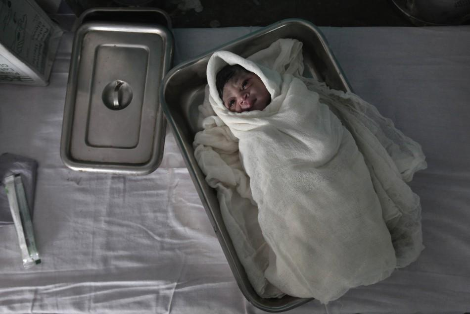 An underweight newborn lies in a tray inside a hospital delivery room in northwestern India