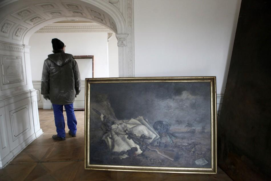 A worker stands next to a painting by German painter Reumann at the Doksany Monastery near Prague