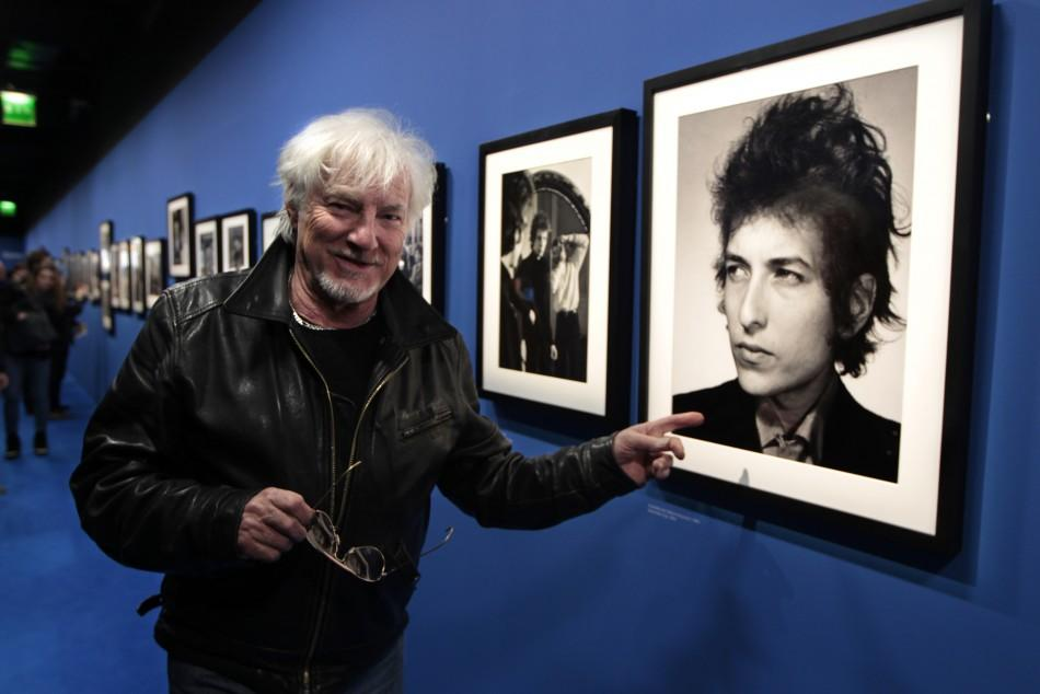 French singer Hugues Aufray points at a photograph of Dylan at the museum of the Cite de la Musique in Paris