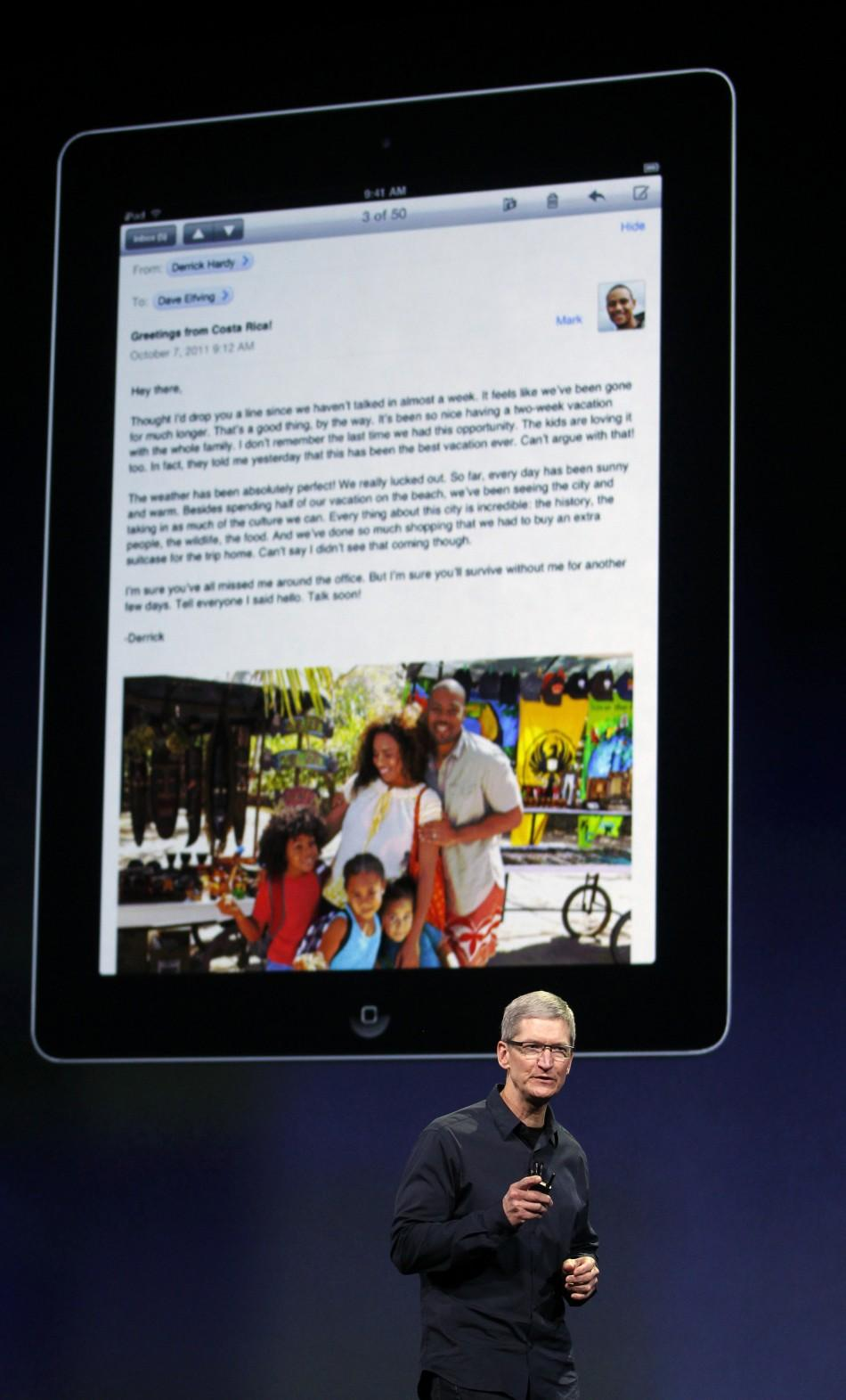 Apple CEO Cook speaks during an Apple event as an image of the old iPad is projected on the screen behind him in San Francisco