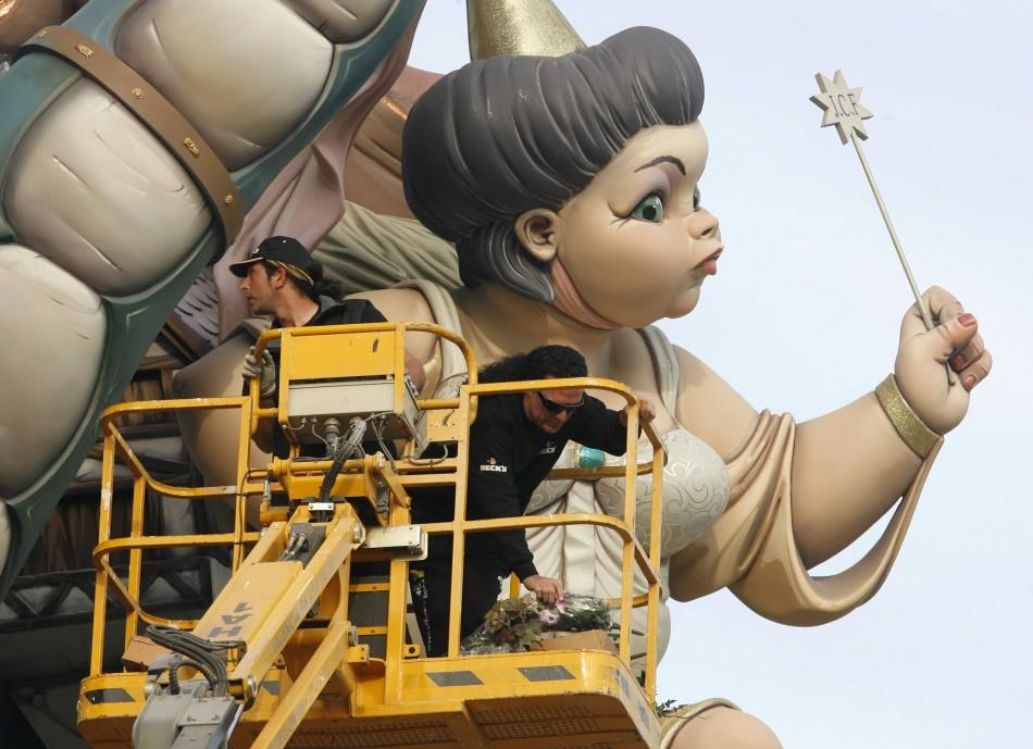 Craftsmen add finishing touches to a figure during the last preparations ahead of the 'Fallas' festival in Valencia
