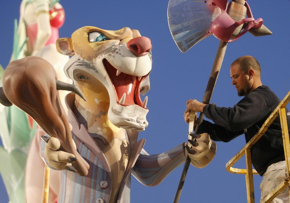 Man puts finishing touches to a falla statue during Fallas festival in Valencia.