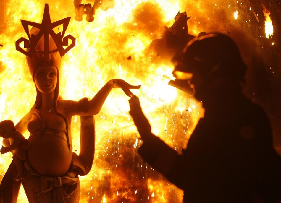A fireman controls a burning effigy during finale of Fallas festival, which welcomes spring and honours Saint Joseph's Day, in Valencia