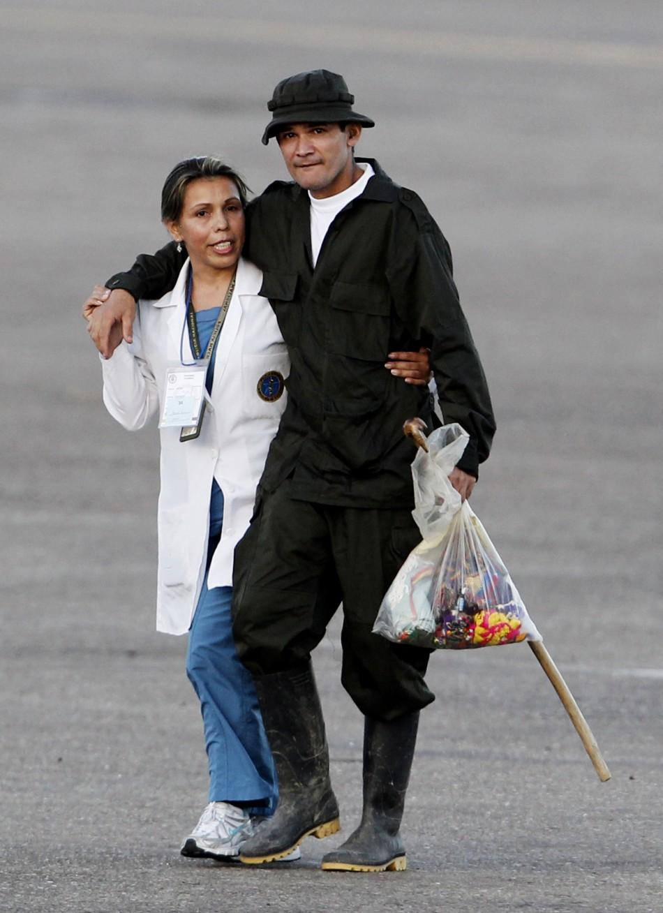 A recently freed hostage walks with a medical personnel as they arrive at Villavicencio's airport