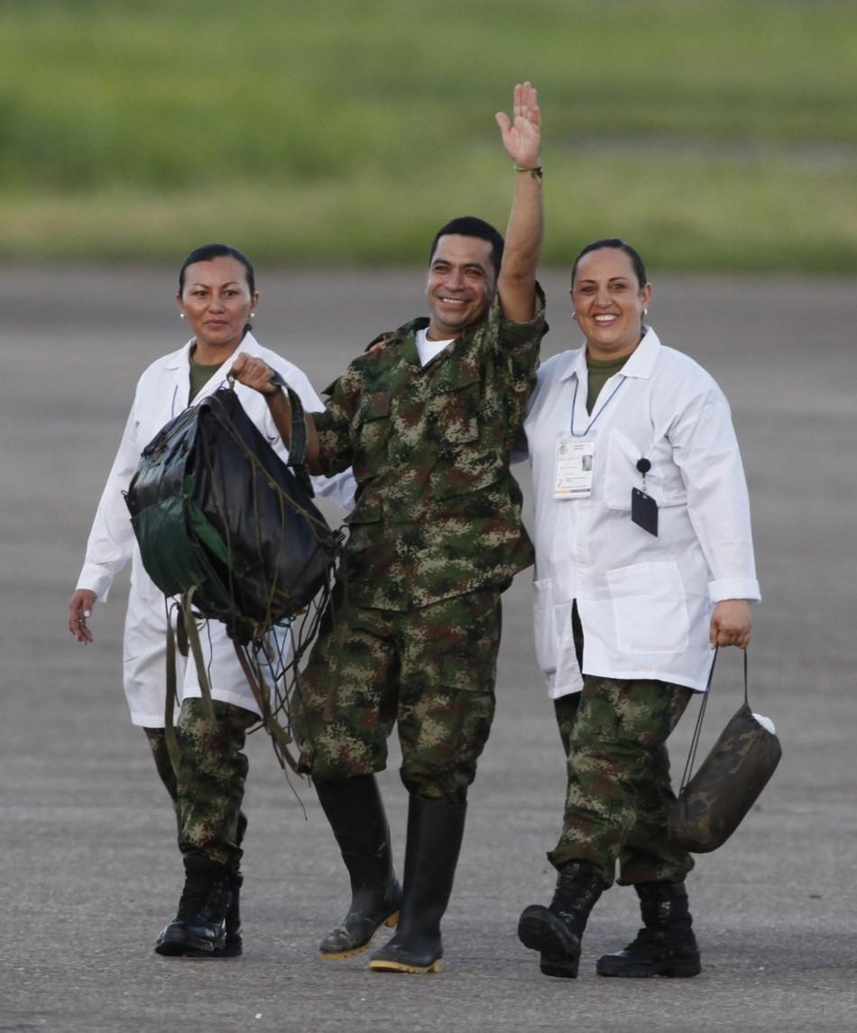 A soldier held hostage by FARC rebels waves next to medical personnel as he arrives at Villavicencio's airport after being