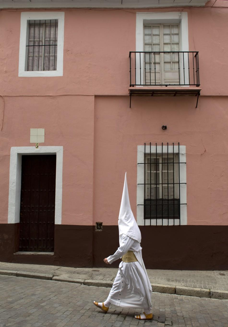 "Penitents of ""La Candelaria"" brotherhood walk to their churchduring Holy Week in Seville"