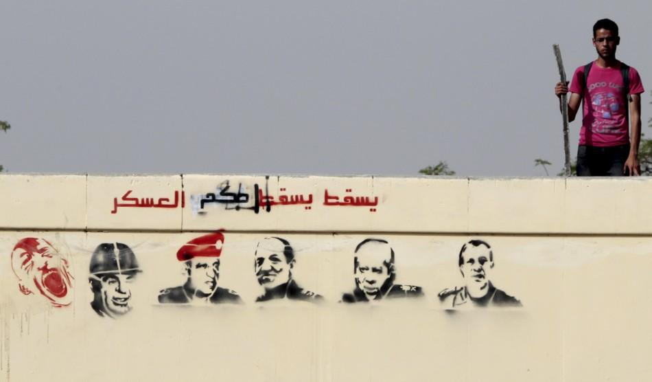 An Egyptian anti-military protester takes his position on a bridge with stencilled paintings depicting the Egyptian military council members, at Abbasiya Square in Cairo May 2, 2012. Egypt's military might hand over to civilian rule earlier than plan