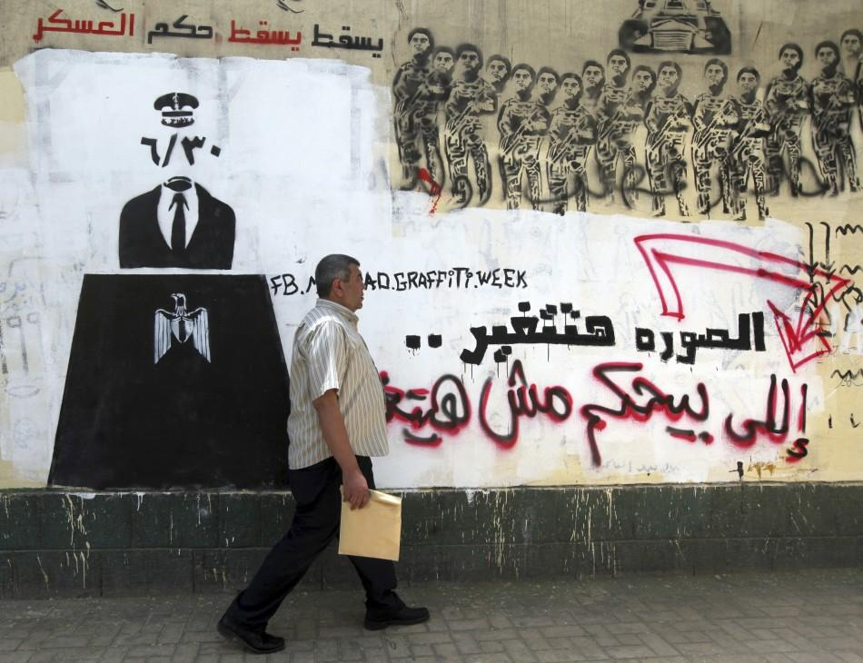 An Egyptian man walks in front of a wall sprayed with graffiti depicting the ruling military council controlling the presidential elections near Tahrir Square in downtown Cairo May 16, 2012. Voting starts in Egypt's presidential election on May 23-24