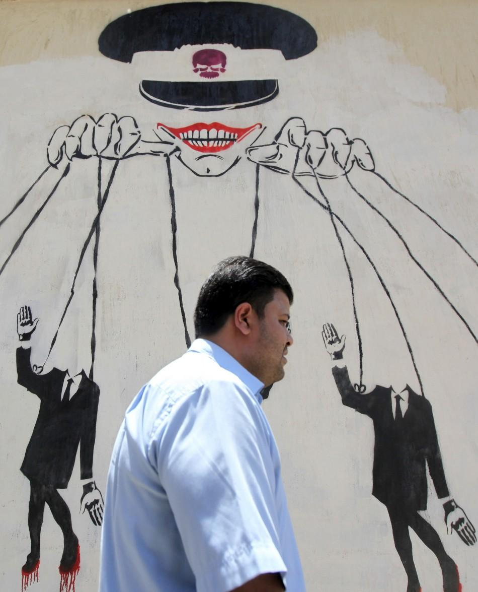 An Egyptian man walks in front of a wall sprayed with graffiti, depicting the ruling military council controlling the presidential elections as a puppet show, near Tahrir Square in downtown Cairo May 16, 2012. Voting starts in Egypt's presidential el