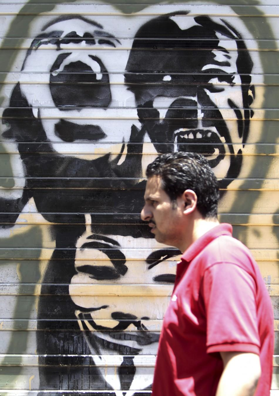 An Egyptian man walks in front of a wall sprayed with graffiti depicting protesters shouting, near Tahrir Square in downtown Cairo