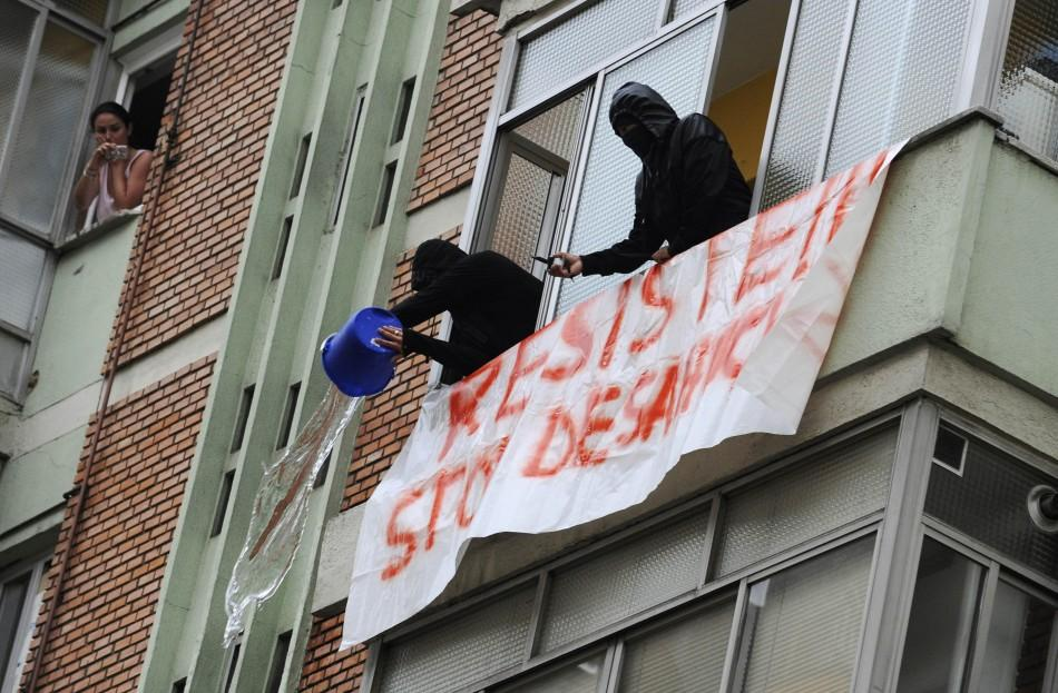 Stop Desahucios activists dump water on riot police to prevent them from executing a June 27 eviction in Oviedo, Spain.