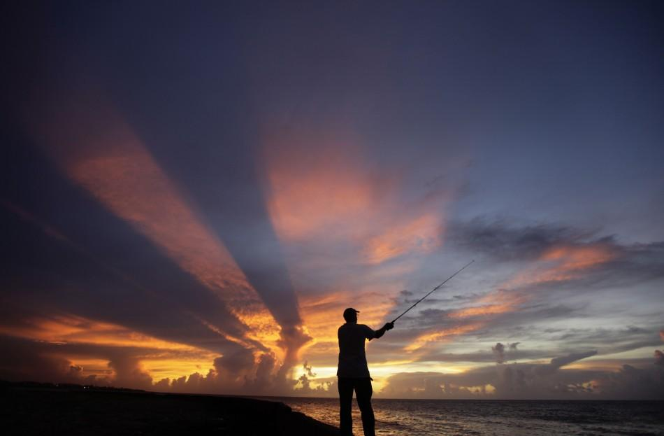 A fisherman casts his line as the sun sets on the outskirts of Havana