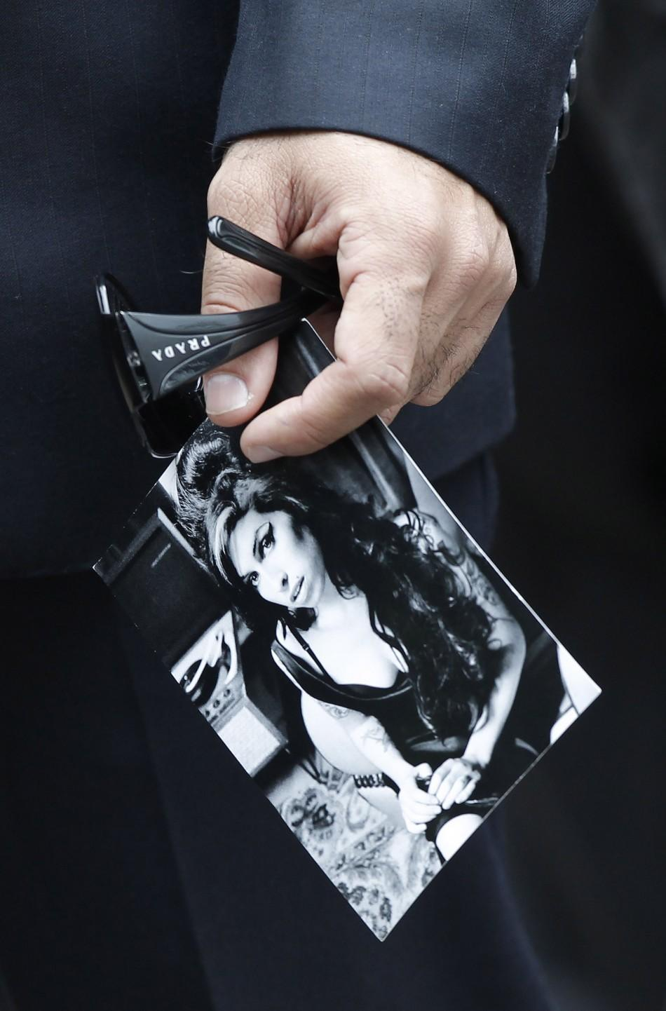 A man holds an invitation bearing a picture of British singer Amy Winehouse before her funeral at Golders Green Crematorium, in north London