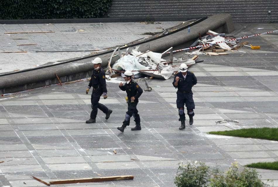 Norwegian policemen inspect the blast site in front of the destroyed government building in Oslo