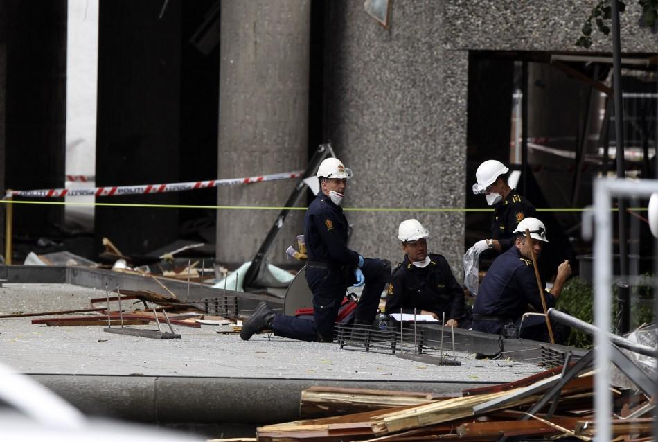 Police investigators work in front of destroyed government building in Oslo