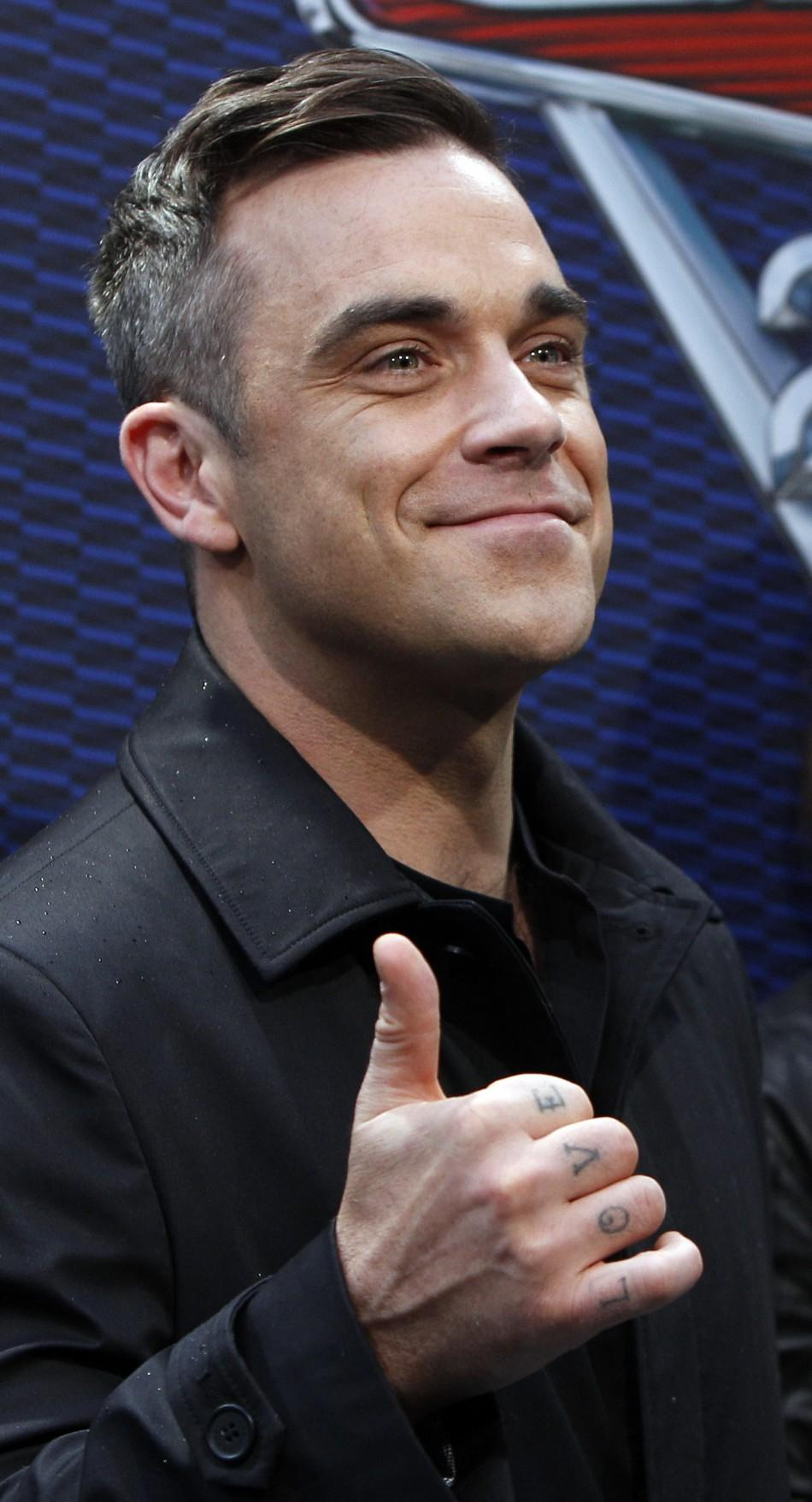 "British singer Robbie Williams gestures as he arrives on the red carpet for the German premiere of ""Cars 2"" in Munich"