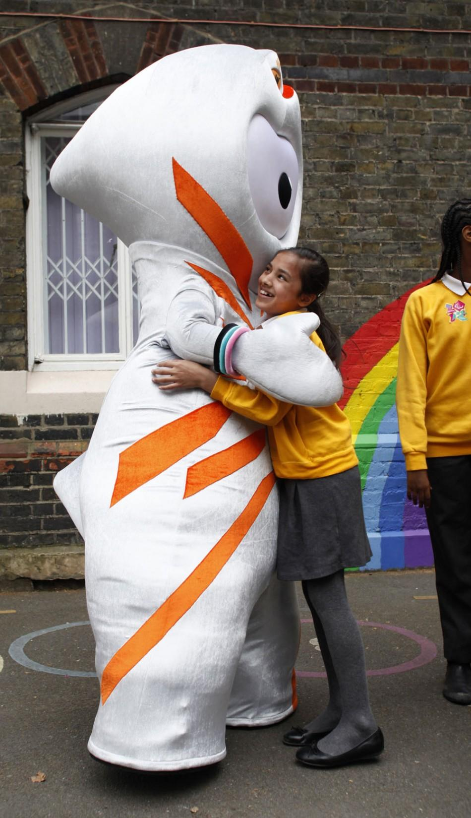 The 2012 Olympic mascot Wenlock hugs a student