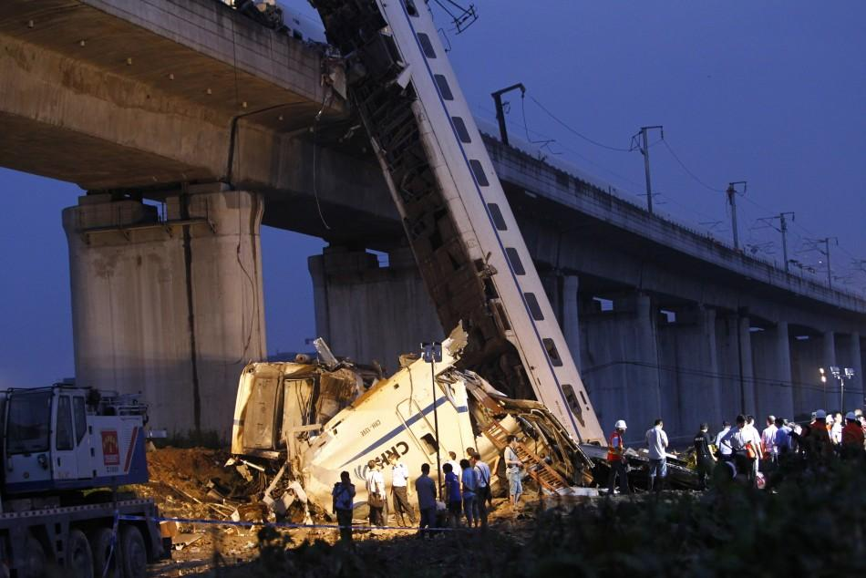 Rescuers carry out rescue operations after two carriages from a bullet train derailed and fell off a bridge in Wenzhou, Zhejiang province