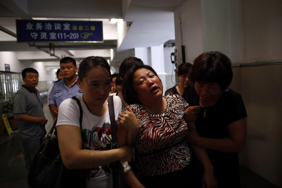 A woman cries as relatives console her inside a morgue where people had gathered to search for their missing kin who were passengers on two bullet trains that had crashed in Wenzhou, Zhejiang province