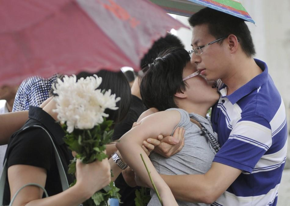 A woman collapses in a man's arms as they mourn for their family members who were victims of the train accident in Wenzhou, Zhejiang province