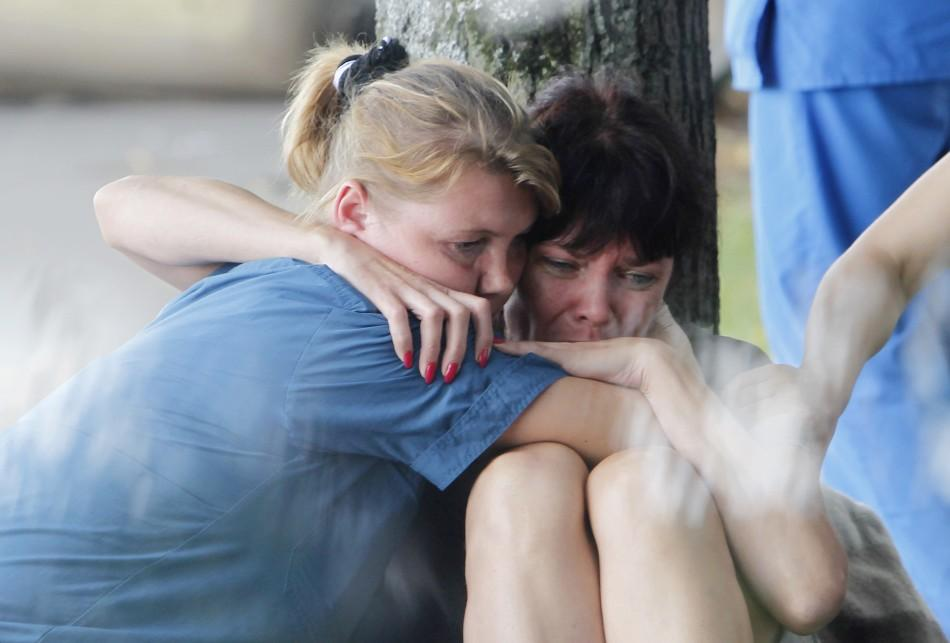 A woman is comforted by a Russian emergency ministry worker (L) on the banks of the Moscow river following a crash between a pleasure boat and barge in Moscow.