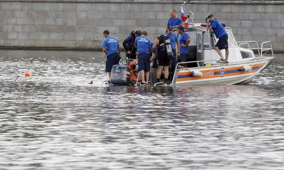 Emergency workers look for survivors following a crash between a private boat and river barge on the Moscow river in Moscow.