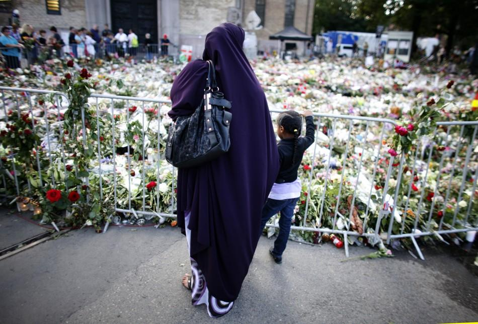 A Muslim woman pays her respects for the victims of last Friday's attacks in front of a sea of flowers outside the Oslo cathedral