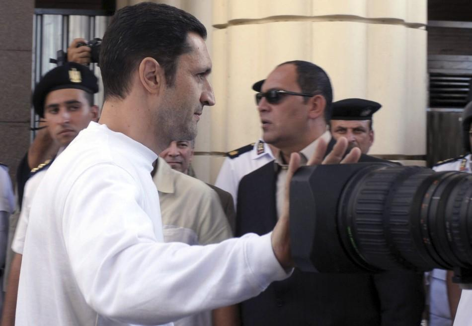 Mubarak, one of former Egyptian president Hosni Mubarak's two sons, covers camera as he leaves courtroom during trial of his father, his brother and himself in Cairo
