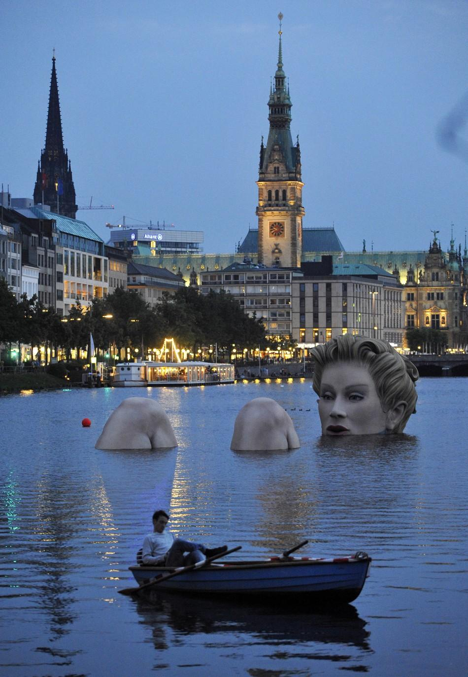 Man in a rowing boat floats near a 'mermaid' sculpture created by Oliver Voss on Alster lake in Hamburg