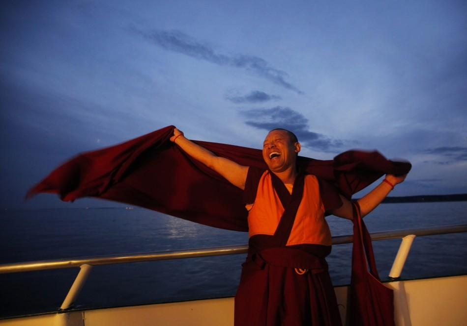 "A Buddhist monk laughs during the release of lobsters back into the ocean on ""Chokhor Duchen"" in the waters off Gloucester"